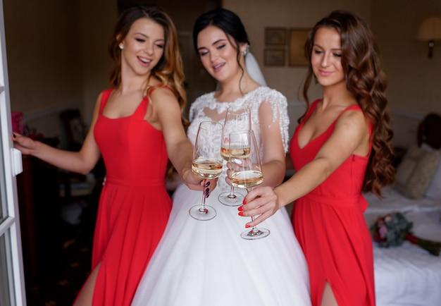 Bruidsmeisjes gekleed in rode jurken drinken wijn met bruid in de kamer