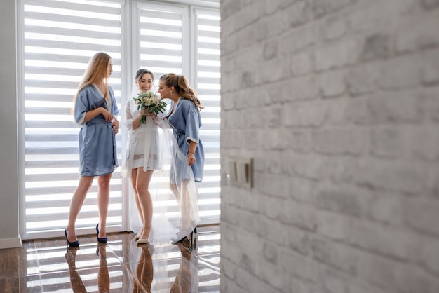 Bruidsmeisjes met bruid gekleed in zijdezachte nachtkleding ruiken de geur van een bruidsboeket