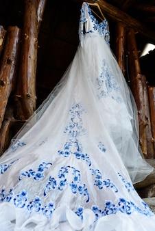 Bruidsmeisjesjurk in de stijl van gzhel hangend aan een houten balk in de ingangsopening van het huis