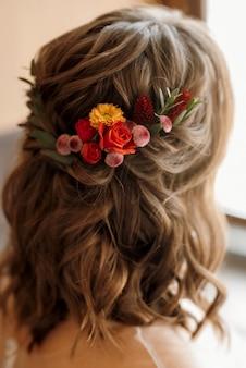Bruidsmeisjeskapsel aan de achterkant met rode bloemen in het haar