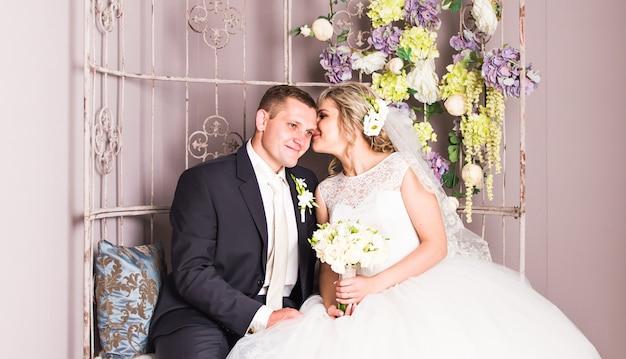 Bruidspaar binnenshuis knuffelt elkaar. mooi model meisje in witte jurk. man in pak. schoonheid bruid met bruidegom. vrouwelijk en mannelijk portret. vrouw met kanten sluier. leuke dame en knappe jongen