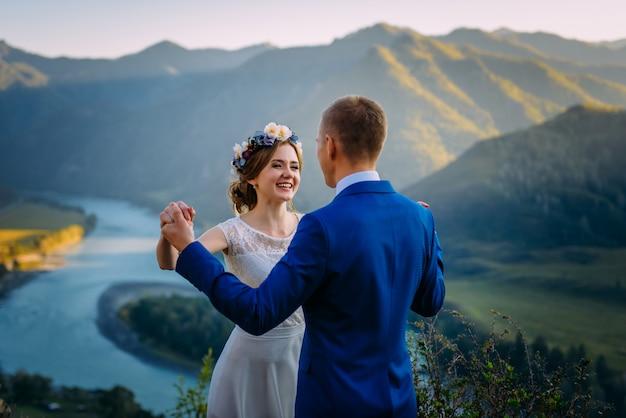 Bruidspaar blijven over het prachtige landschap met bergen en rivier