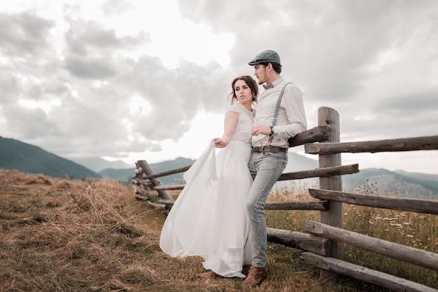 Bruidspaar, bruidegom en bruid in de buurt van huwelijksboog op een achtergrond bergrivier
