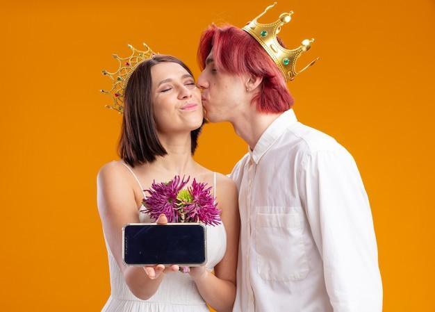 Bruidspaar bruidegom en bruid met boeket bloemen in trouwjurk met gouden kronen, bruidegom kust zijn bruid terwijl ze smartphone toont