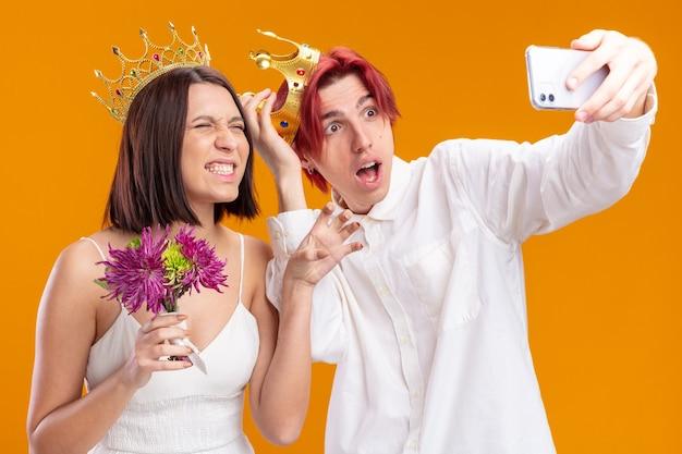 Bruidspaar bruidegom en bruid met boeket bloemen in trouwjurk met gouden kronen, verward en verrast terwijl ze selfie maken met smartphone