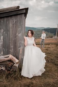 Bruidspaar, bruidegom en bruid poseren in landelijk gebied