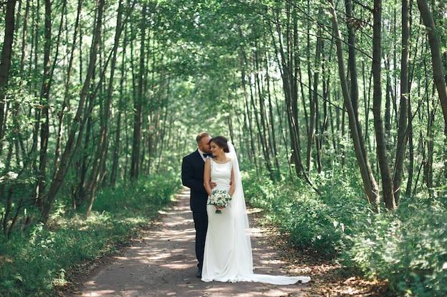 Bruidspaar genieten van romantische momenten buiten. bruiloft dag in de zomer. gelukkige emotionele bruid en bruidegom lopen in een groene parkin zonnige dag. bruidegom kussende bruid. bruidegom omarmt bruid in de tuin
