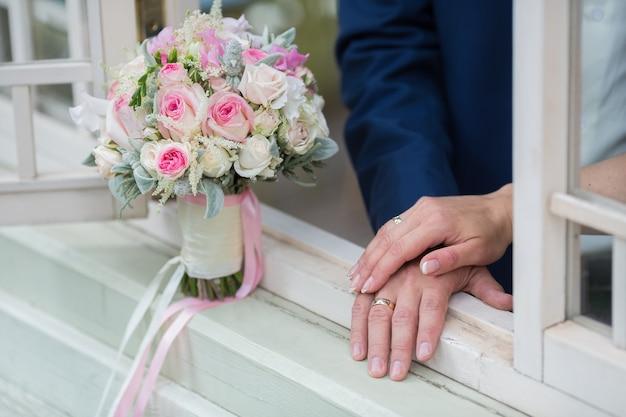 Bruidspaar hand in hand op zomer groene achtergrond met rijke bos roze pioenrozen en lila eustoma rozen bloemen. huwelijksconcept met boeket