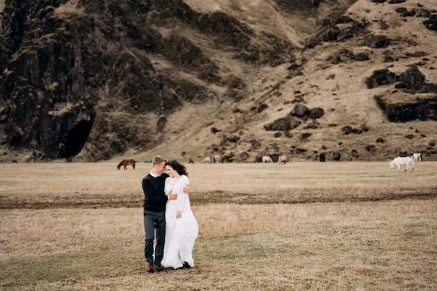 Bruidspaar in de buurt van een rotsachtige berg en grazende paarden in ijsland