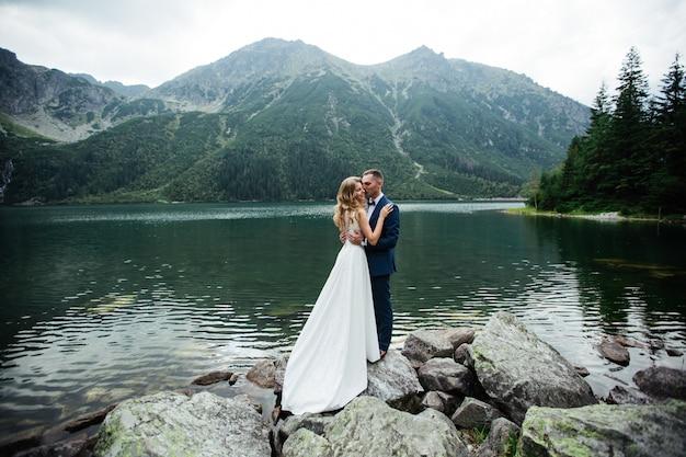 Bruidspaar in een bos in de bergen bij zonsondergang