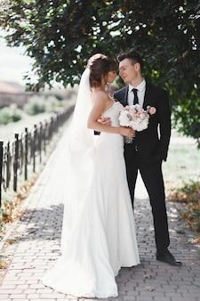 Bruidspaar in het park. bruid in stijlvolle en mooie luxe witte jurk en sluier en boeket in handen. bruidegom in een zwart pak.