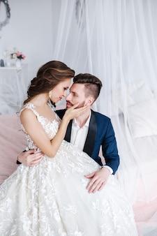 Bruidspaar knuffelen elkaar binnen. mooie modelvrouw in witte kleding. man in pak. schoonheidsbruid met bruidegom.