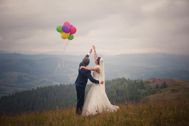 Bruidspaar knuffelen en lanceren van gekleurde ballonnen in de lucht