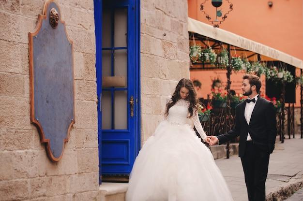Bruidspaar knuffelen in de oude stad. blauwe vintage deuren en café in de oude stad op de achtergrond. stijlvolle bruid in witte lange jurk en bruidegom in pak en strikje. trouwdag.