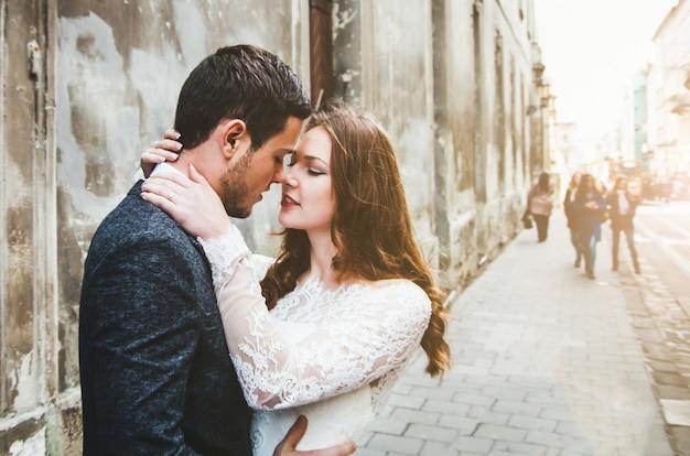 Bruidspaar knuffels in de oude stad. stenen muren van de oude stad op de achtergrond. rustieke bruid met haar naar beneden en bruidegom in grijs pak en vlinderdas. romantische liefde in vintage sfeer straat. liefdesverhaal.