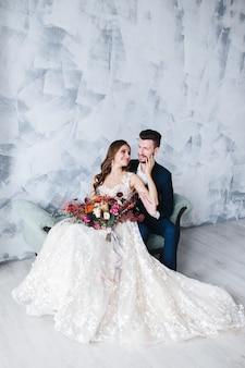 Bruidspaar knuffelt binnenshuis elkaar. mooie modelvrouw in witte kleding. man in pak. schoonheidsbruid met bruidegom