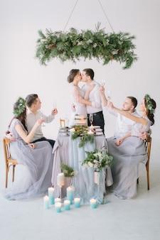 Bruidspaar kussen aan de versierde bruiloft tafel met hun bruidsmeisjes en bruidsjonkers