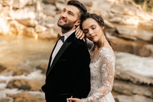 Bruidspaar, liefhebbers op de achtergrond van een stenen rivier.