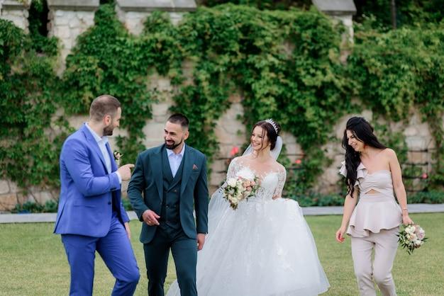 Bruidspaar met beste vrienden lacht buitenshuis in de buurt van de stenen muur bedekt met klimop