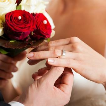 Bruidspaar met boeket en bruidsring