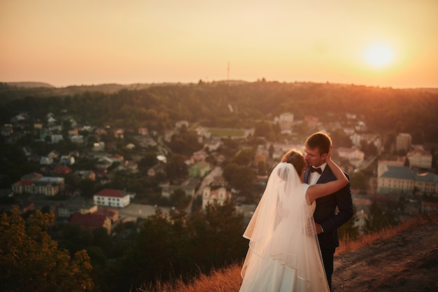 Bruidspaar omarmen bij zonsondergang