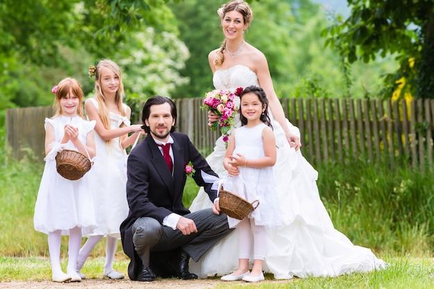 Bruidspaar op bruiloft met bruidsmeisje kinderen