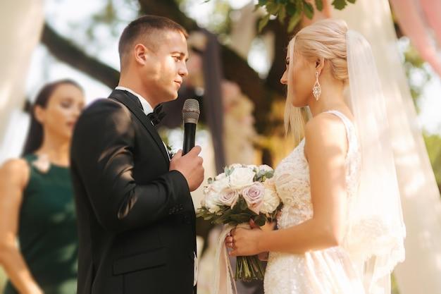 Bruidspaar op ceremonie buiten mooie bruid en knappe bruidegom net getrouwd