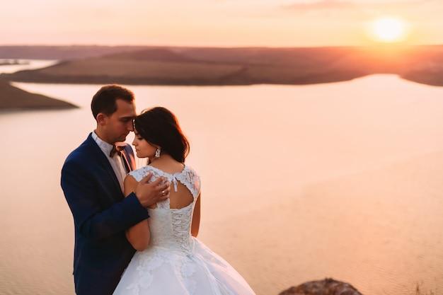 Bruidspaar op zoek naar beneden en romantisch knuffelen bij zonsondergang