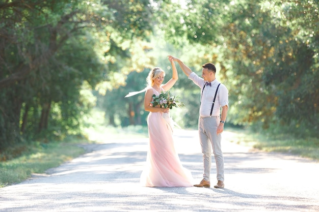 Bruidspaar over de aard in zomerdag. de bruid en bruidegom dansen