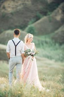 Bruidspaar over de aard in zomerdag. de bruid en bruidegom knuffelen op de bruiloft.