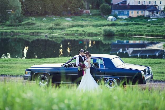 Bruidspaar staat in de buurt van de retro vintage auto