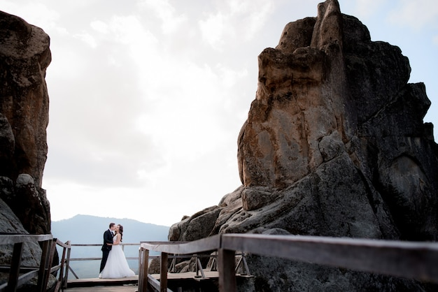 Bruidspaar staat op de houten brug tussen twee hoge kliffen en kussen, bruiloft avontuur