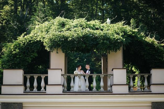 Bruidspaar van bruidegom en bruid staan op een groot schitterend balkon