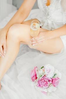 Bruidsprijzen vóór de bruiloft, de bruid in witte lingerie met champagne