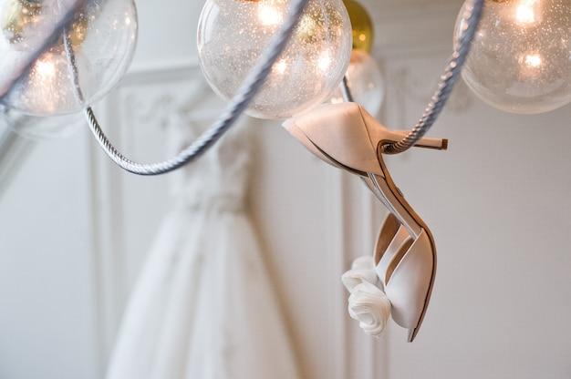 Bruidsschoenen hangen aan de kroonluchter in het interieur van een luxe hotel