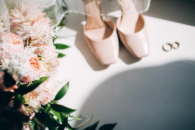 Bruidsschoenen met een boeket met rozen en andere bloemen op de fauteuil