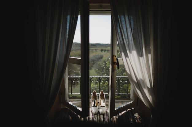 Bruidsschoenen staan op de vensterbank met een prachtig uitzicht erachter