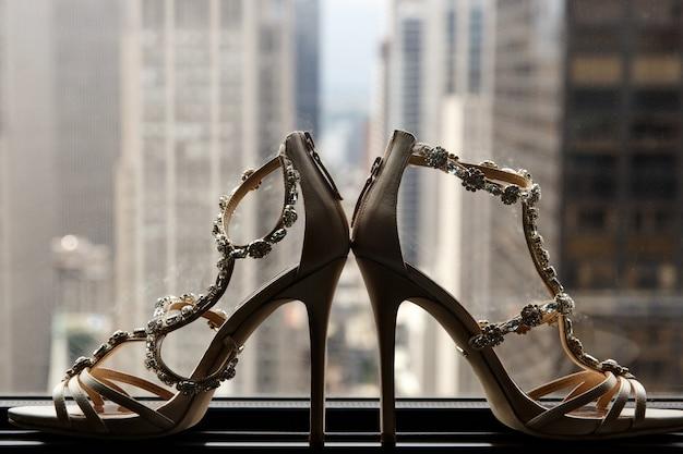 Bruidsschoenen staan op de vensterbank voor het stadsbeeld