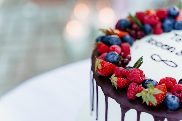 Bruidstaart close-up met aardbeien en bosbessen bovenop. witte smakelijke cake voor ceremonie