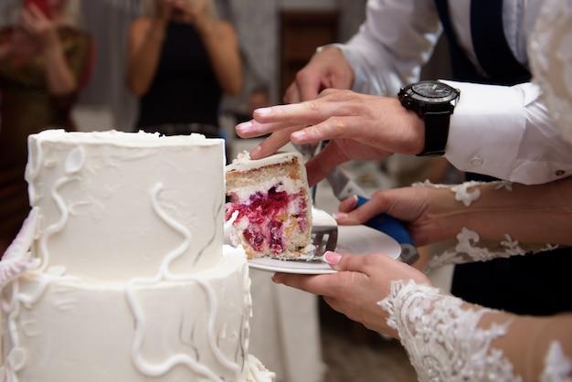 Bruidstaart. een bruid en een bruidegom snijden hun bruidstaart