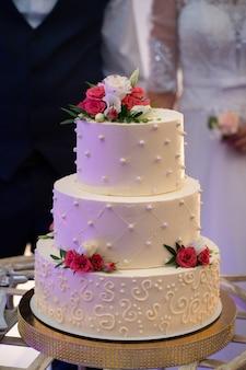 Bruidstaart, handen en het mes, snijden