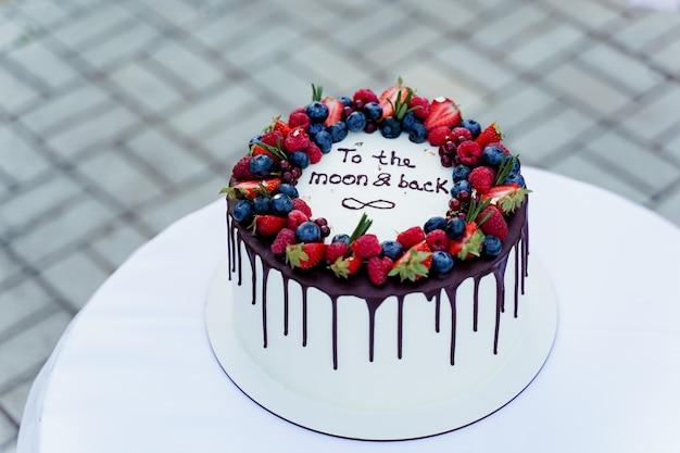 Bruidstaart met aardbeien en bosbessen bovenop. witte smakelijke cake voor ceremonie.