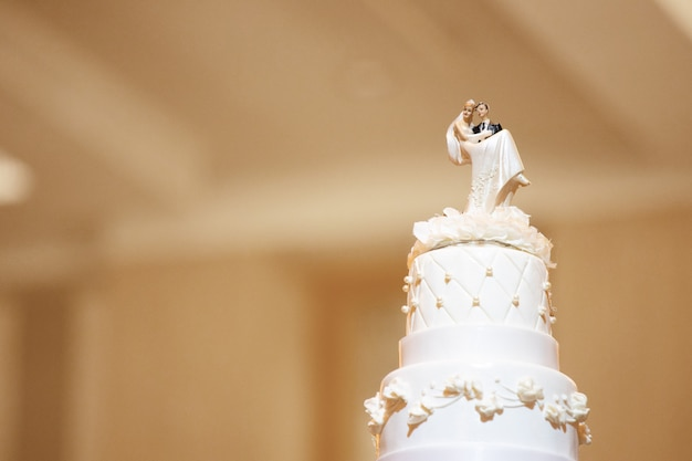 Bruidstaart met bruid en bruidegompoppen op bovenkant met spatie copyspace