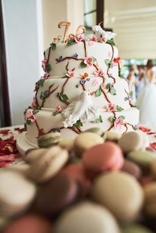 Bruidstaart met decoratieve bloemen, macarons, rode rozen bloemblaadjes en andere verschillende snoepjes op candy bar.