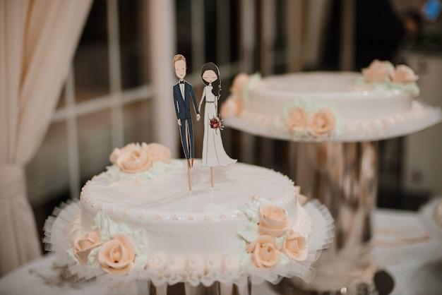 Bruidstaart met grappige beeldjes van de bruidegom en de bruid.