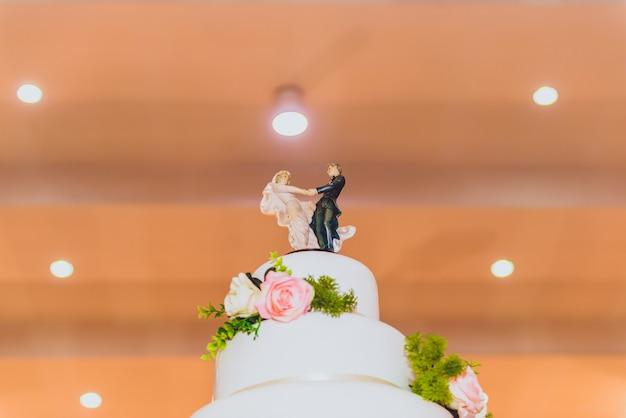 Bruidstaart met versierd met bloemen en kandelaar tijdens huwelijksceremonie