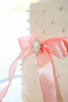 Bruidstaart met wit suikerglazuur en roze boog