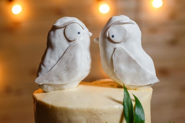 Bruidstaart op meerdere niveaus, gedecoreerd met bloemen, groen en creatieve vogels