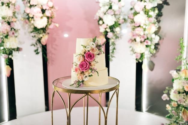 Bruidstaart op tafel met florale achtergrond
