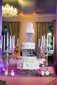 Bruidstaart versierd met crèmekleurige bloemen op een standaard.